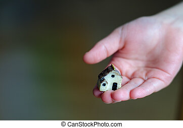 Closeup of tiny plastic house in the child's hand