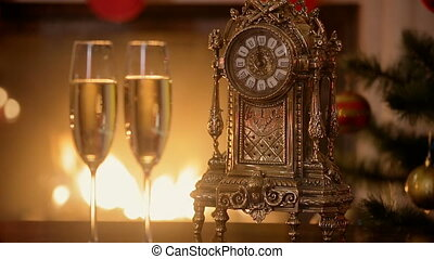 Closeup of two glasses of champagne next to old clock counting minutes to the New Year on table next to burning fireplace