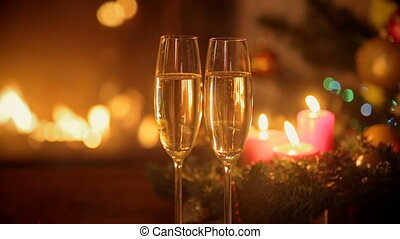 Closeup of two glasses of fizzy champagne in front of burning fireplace. Decorated Christmas tree and burning candles on background.