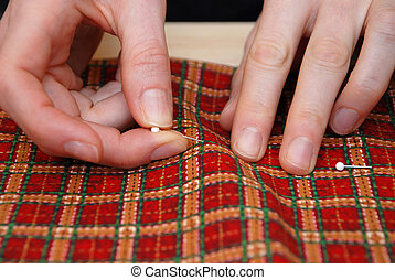 Closeup of two hands sticking pins into festive red plaid fabric