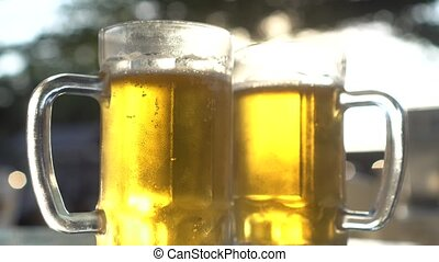 Closeup of two lager beer mugs with sun rays - Closeup of...