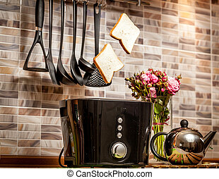 Closeup of two slices of bread popping out of toaster on kitchen