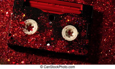 Closeup of video cassette on red glitter background