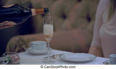 Closeup of waiter pouring pink champagne