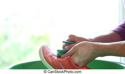 Closeup of washing shoes using brush