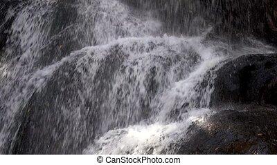 Closeup of Water Cascading On Rocks In Waterfall.