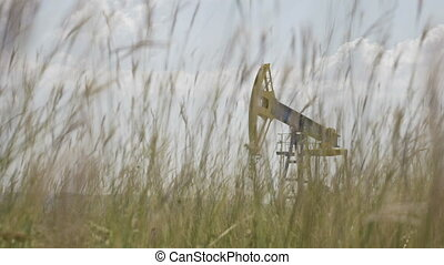 Closeup of wheat field with oil industry pump unit...