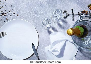 Closeup of white plate, fork, knife, green bottle of...