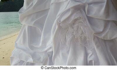 closeup of white wedding dress hangs on green tree - closeup...