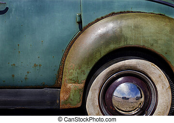 closeup of whitewall Tires, fender and hubcap on Old Junk Vintage Car with peeling paint