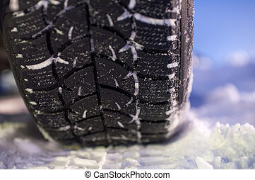 Closeup of winter tyre on the road, selective focus, shalow depth of field