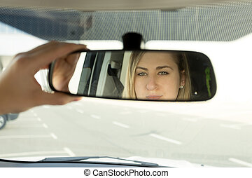 Closeup of woman adjusting car mirror and looking in the reflection