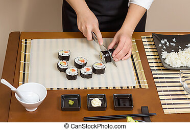 Closeup of woman chef cutting japanese sushi rolls with rice...