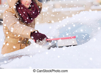 closeup of woman cleaning snow from car