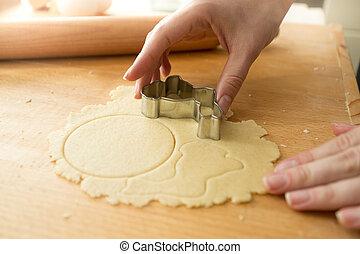 Closeup of woman cutting dough with metal form