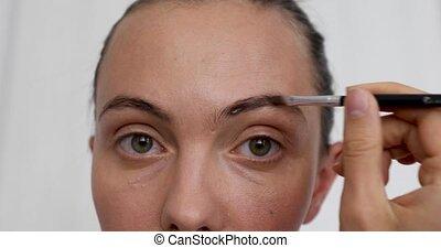 Closeup of woman doing makeup of eyebrows - Closeup of adult...