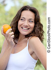 Closeup of woman eating an orange
