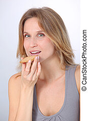 Closeup of woman eating cookie