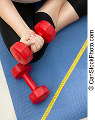Closeup of woman exercising on fitness mat and lifting red dumbbell