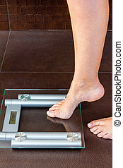 Closeup of woman foot uploading to bathroom scale. Health and weight concept