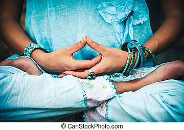 closeup of woman hands and legs in meditative pose practice yoga outdoor shot