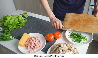 Closeup of woman hands cutting red tomato on wooden board for pizza in the kitchen at home