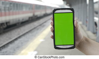 Closeup of woman hands holding smartphone with green screen chroma key in train station