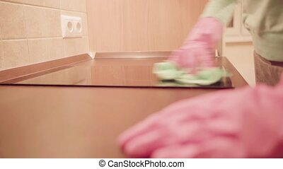Closeup of woman hands in pink rubber glove with rag cleaning kitchen table. Housework and housekeeping concept