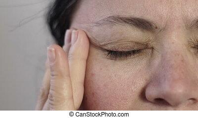 Closeup of Woman Massaging Her Headache Pain