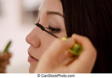 Closeup of woman putting mascara on