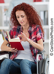 closeup of woman reading book in wheelchair