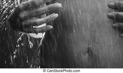 Closeup of woman stomach with touching hands under outdoor shower