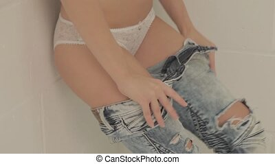 Closeup of woman taking off jeans - Closeup of woman in...