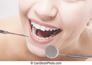 Closeup of Woman Teeth with Dental tools