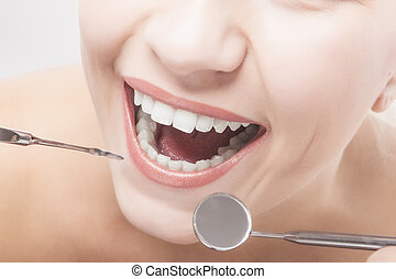 Closeup of Woman Teeth with Dental tools