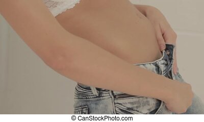 Closeup of woman unzipping jeans - Closeup of woman in white...