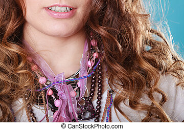 Closeup of woman wearing jewelry necklaces.