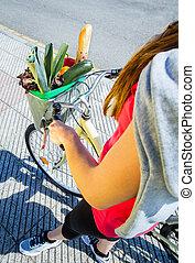 Closeup of woman winth groceries in a basket bike