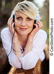 Closeup Of Woman With Headphones Lying On Log