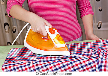 woman's hand ironing clothes