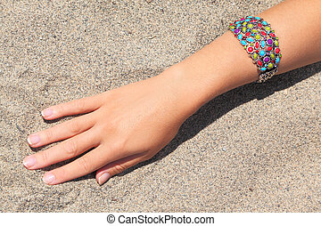 closeup of womans hand with multicolored bracelet on sand, sunny day