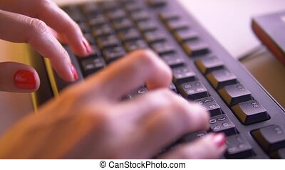 Closeup of woman's hands typing on the keyboard