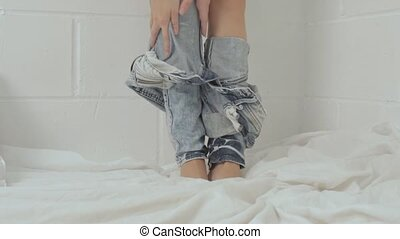 Closeup of woman's leg while taking off jeans - Closeup of...