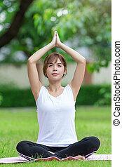 Closeup of women doing yoga in park
