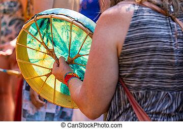 closeup of women playing sacred drum