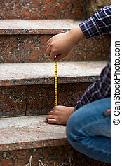 Closeup of worker measuring height of stone steps - Closeup...