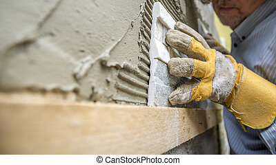 Closeup of workman carefully positioning an ornamental tile in a glue