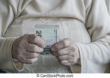 Closeup of wrinkled hand holding turkish lira banknotes