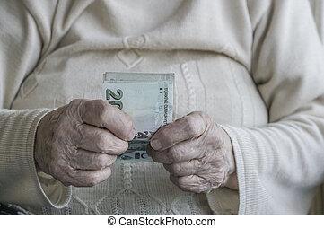 Closeup of wrinkled hand holding turkish lira banknotes