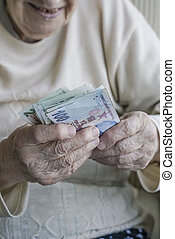 Closeup of wrinkled hands holding turkish lira banknotes